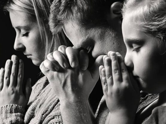 people praying at a funeral